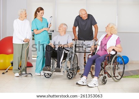 Group of senior people with and without disabilities with geriatric nurse at physiotherapy - stock photo
