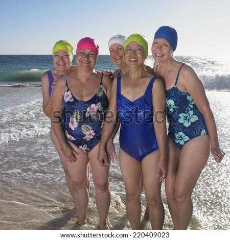 Group of senior women in bathing suits at beach - stock photo