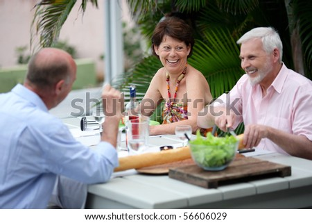 Group of seniors having a dinner on a terrace - stock photo