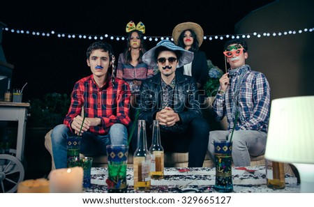 Group of serious young friends with costumes and atrezzo looking to the camera before to start a outdoors party. Friendship and celebrations concept. - stock photo