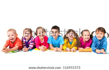 Group of seven children are lying on floor with copybooks together - stock photo