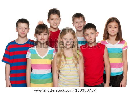 Group of seven children are standing on the white background; focus is on the central girl - stock photo