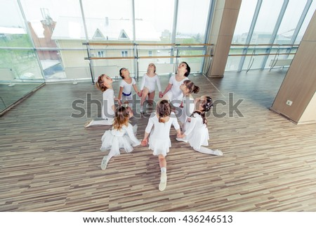 group of seven little ballerinas sitting on the floor. They are good friend and amazing dance performers - stock photo