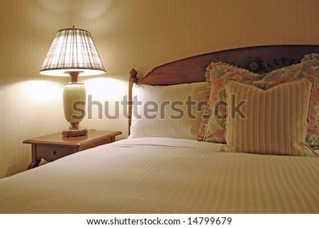 Group of several pillows on a bed with headboard - stock photo