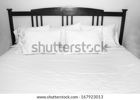 Group of several white pillows on a white bed with wooden headboard - stock photo