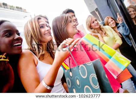 Group of shopping people holding bags looking at a window - stock photo