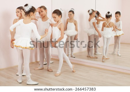 Group of six little ballerinas posing together and practicing for performance. They are good friend and amazing dance performers - stock photo