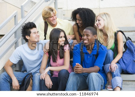 Group of six students sitting on outside on stairs - stock photo