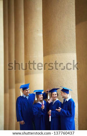 Group of smart students in graduation gowns having chat - stock photo