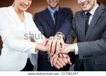 Group of smiling business partners in suits making pile of hands - stock photo