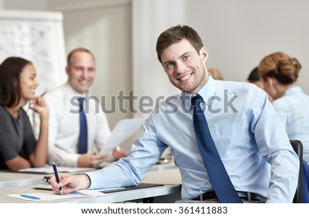 group of smiling businesspeople meeting in office - stock photo