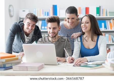 Group of smiling college students using a laptop and studying together in the classroom, education and friendship concept - stock photo