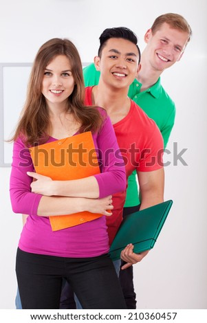 Group of smiling college students with folders - stock photo