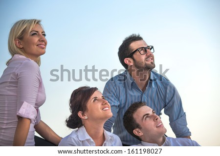 Group of smiling corporate people sitting outside looking up - stock photo