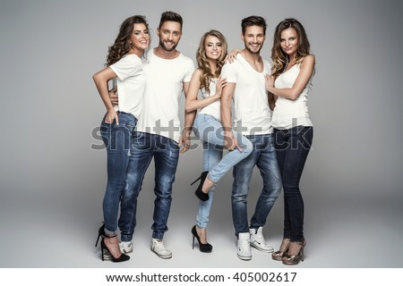 Group of smiling friends in fashionable jeans - stock photo