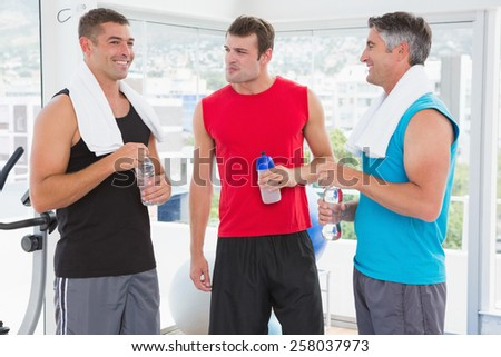 Group of smiling men talking each other in fitness studio - stock photo