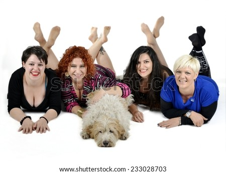 Group of smiling multiethnic adult women friends with different hair colors in elegant clothes lying with adorable dog (spinone italiano). Isolated on white background. - stock photo