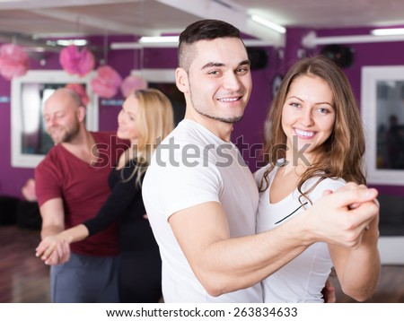 Group of smiling positive young adults dancing at dance class. Focus on guy - stock photo