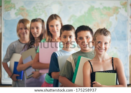 Group of smiling primary school students posing in their classroom in front of a map of the world. - stock photo