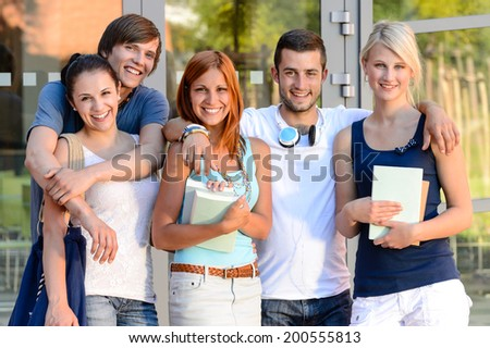 Group of smiling students standing front of college campus summer - stock photo