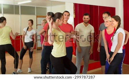 Group of smiling young adults with trainer in a dance studio. Selective focus
