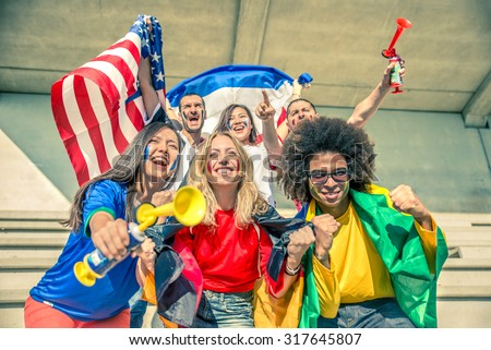 Group of sport supporters at stadium - Fans of diverse nations screaming to support their teams - Multi-ethnic people having fun and celebrating on tribune at a sport event  - stock photo