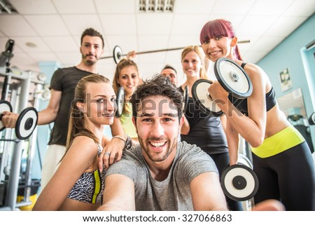 Group of sportive people in a gym taking selfie - Happy sporty friends in a weight room while training - Concepts about lifestyle and sport in a fitness club - stock photo
