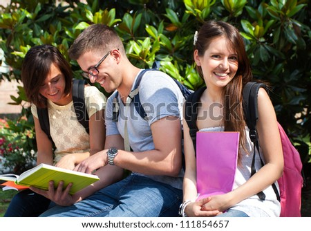 Group of student reading a book together in the park - stock photo
