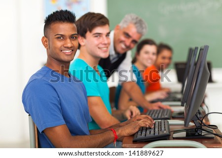 group of students and teacher in computer class looking at the camera - stock photo