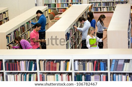 Group of students at the library looking for books - stock photo