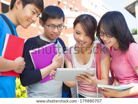 group of students discussing homework by using tablet - stock photo
