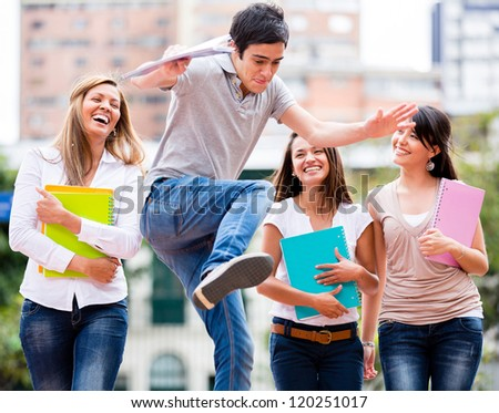 Group of students having fun looking at a man jumping - stock photo