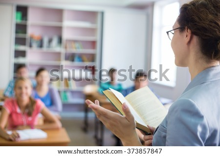 group of students listening to the teacher in the classroom at school - stock photo