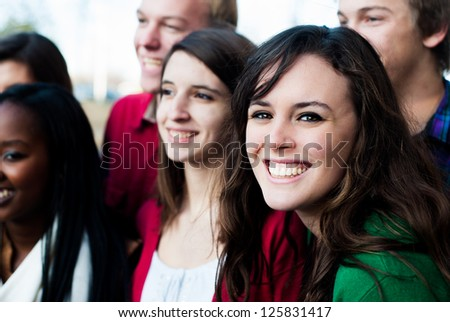 Group of students outside smiling with focus on one - stock photo