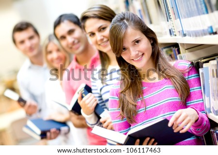 Group of students reading books at the library and smiling - stock photo
