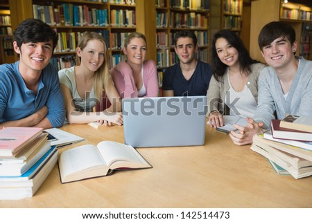 Group of students sitting at a table in a library while using the laptop and learning - stock photo