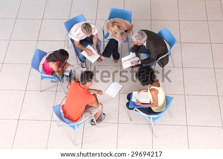 Group of students sitting down and studying with lecturer - stock photo
