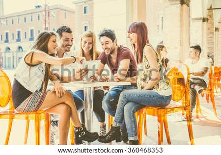 Group of students sitting in a cafe bar looking at tablet - Young cheerful friends having fun with portable computer - Active people watching a funny streaming movie online - stock photo