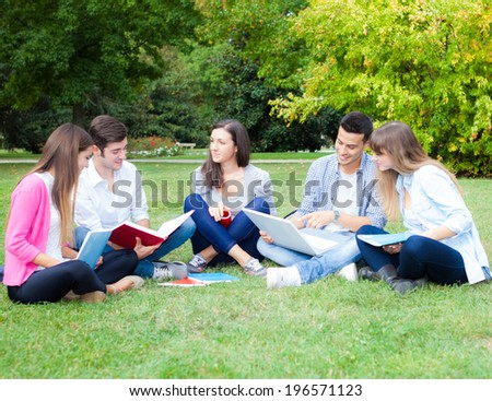 Group of students sitting on the grass - stock photo