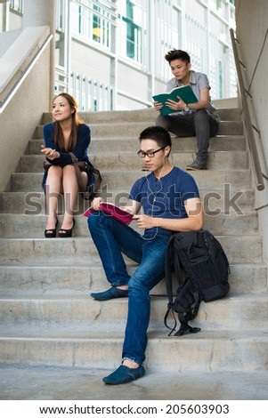 Group of students sitting on the stairs - stock photo