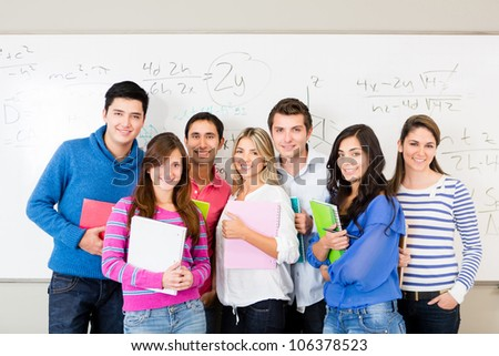 Group of students smiling and holding notebooks - stock photo