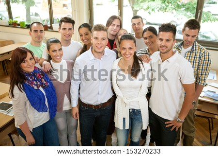 Group of students standing and smiling  in classroom - stock photo