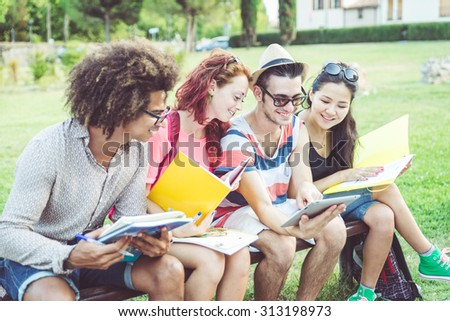 group of students studying at the park after school. concept about education and technology - stock photo