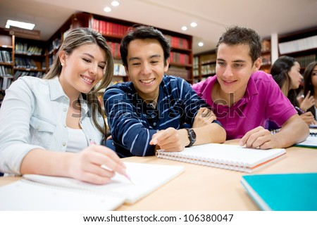Group of students studying together at the library - stock photo