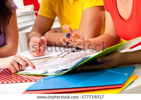 Group of students studying together from notes on a desk - stock photo