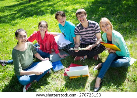 Group of students studying together in campus ground - stock photo