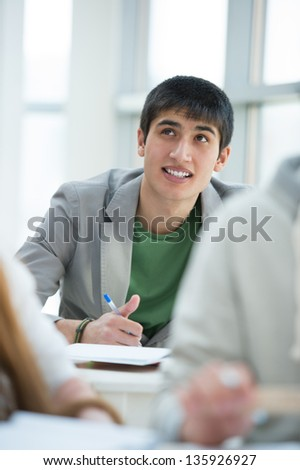 Group of students studying together in classroom. Mixed race student dreaming and looking upwards while making notes - stock photo