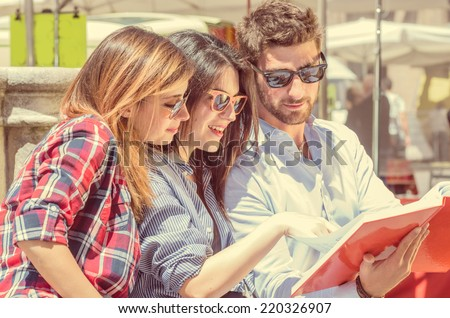 group of students. two girls and one boy studying with interest on a book  - stock photo
