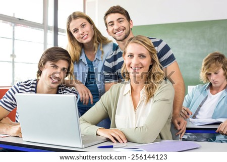 Group of students using laptop in classroom - stock photo