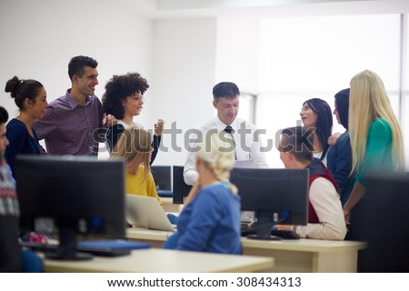 group of students with teacher in computer lab classrom learrning lessons,  get help and support - stock photo